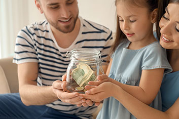 young family holding jar with money